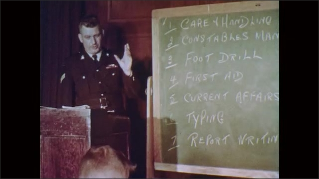 1960s: Officer checks gun and hands it back to man.  Men sit and take notes.  Man stands at chalkboard.