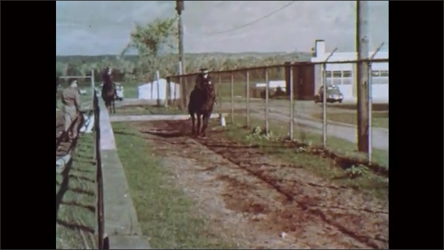 1960s: Policemen gallop on horses.  Horses jump over small fences.