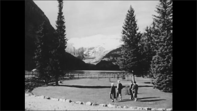 1950s: Family poses for a picture in front of Lake Louise. Views of the Rocky Mountains.