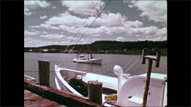 1950s CANADA: boat in harbour. Boat moored to jetty. Boats in fishing village. Seagulls above boats