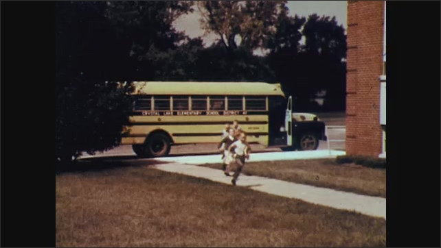1960s: square-ish building façade, children exit school bus, run down sidewalk, last child turns around, picks up something he dropped, continues running