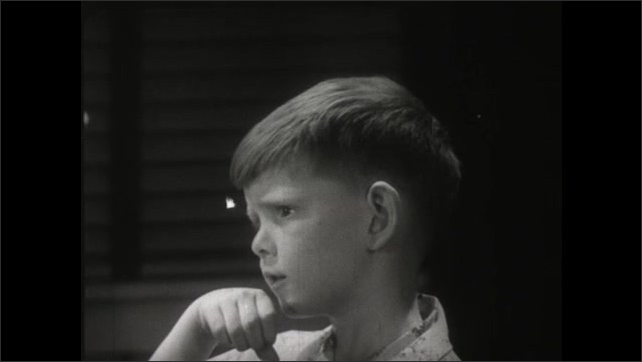 UNITED STATES 1950s: Trying to imitate a cat, a boy licks his hands.
