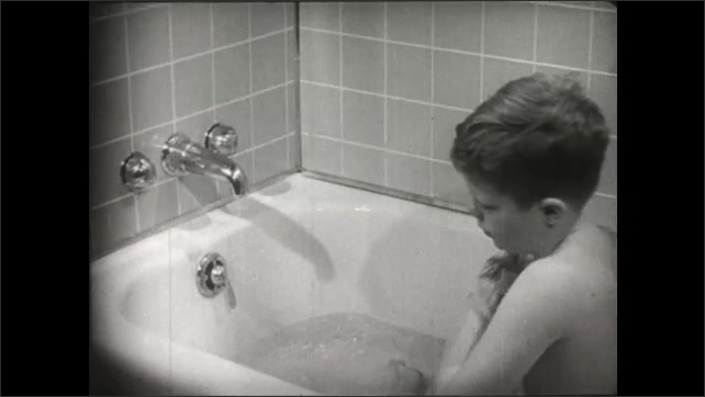 UNITED STATES 1950s: A boy soaks in the bathtub while cleaning himself.
