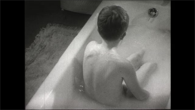 UNITED STATES 1950s: A boy washes himself while taking a bath.