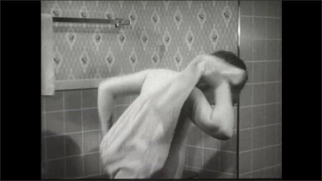 UNITED STATES 1950s: A young boy uses a towel to dry himself after taking a bath.