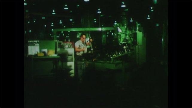 1970s: Reel to reel tape turns. Liquid spews out of hose as drill burrows into metal. Man at work in machine shop. Reel to reel tape. Man watches automated drill press. Reel to reel tape.