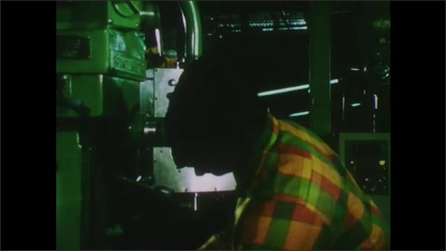 1970s: Liquid spews out of hose as drill burrows into metal. Man works automated drill press.