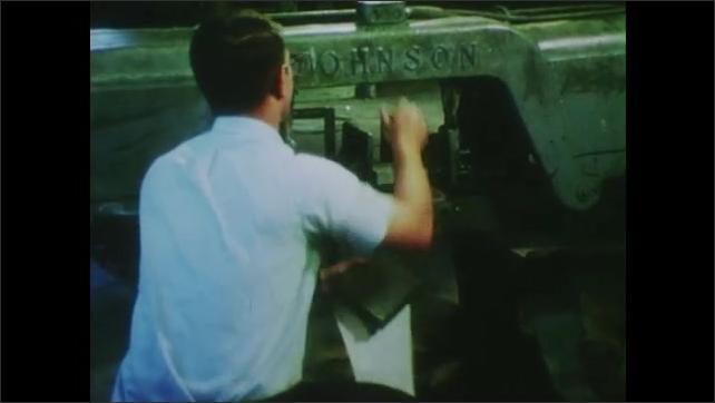 1970s: Man in machine shop uses drill press. Drill press drills into metal. Man inspects block of metal from machine.