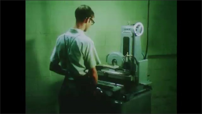 1970s: UNITED STATES: student works with machine. Surface grinder machine. Boy uses surface grinder.