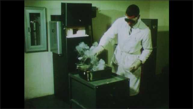 1970s: UNITED STATES: teacher instructs student in properties of metals. Metal in lab. Student works at tape printer.