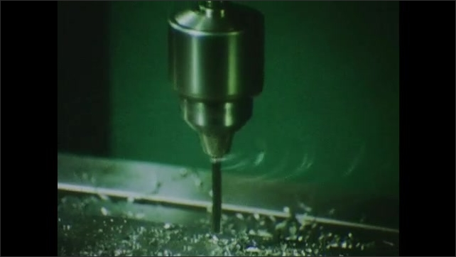 1970s: UNITED STATES: tape-o-matic machine. Drill makes holes in metal. Metal shavings by drill.