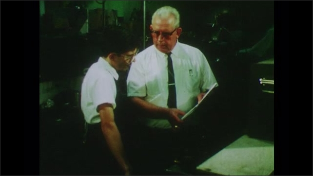 1970s: UNITED STATES: man designs machine to make capacitor. Method specialist solves mechanical problem with student. Boy with glasses.