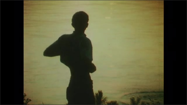 1970s: UNITED STATES: boy throws stone across water. Boy dusts off hands. Skimming stone bounces on water.