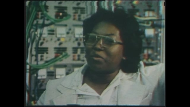 1970s: Shirley Chevalier, Electrical Engineer is interviewed in front of panel of electronics.