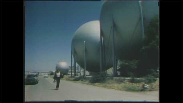 1970s: Susan Norman, Research Scientist meets with other NASA workers in a meeting room. Sharon Orkansky, a computer programmer at NASA, walks alongside round storage tanks on a road.