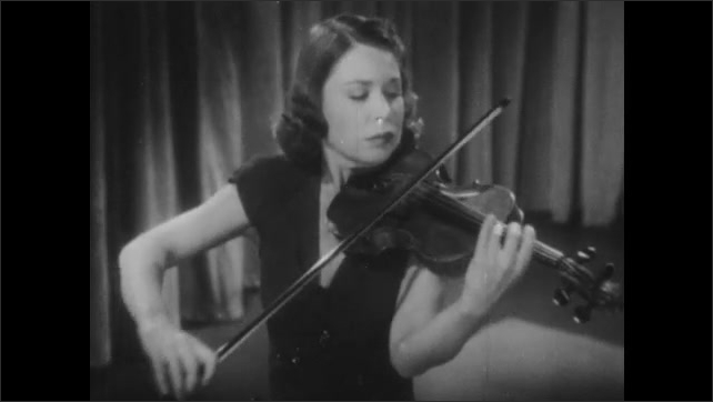 1950s: Carroll Glenn plays violin on stage.