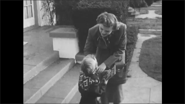 1950s: UNITED STATES: Lady collects child from school. Lady smiles at boy. Boy smiles at lady. Feet on sidewalk