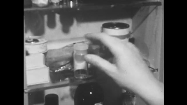 1950s: UNITED STATES: hand opens medicine cabinet. Empty bottle. Lady holds hand to head.