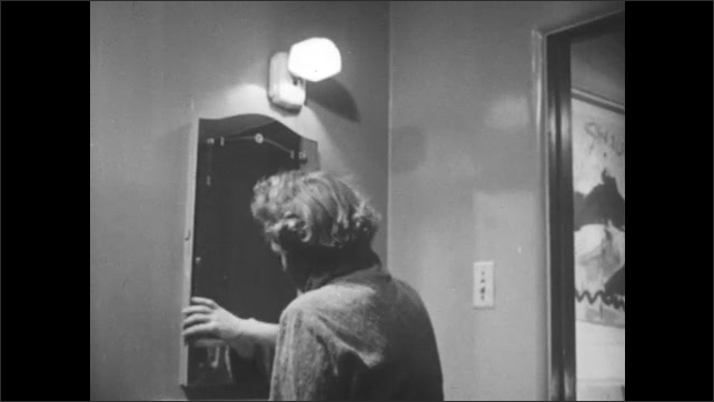 1950s: UNITED STATES: Lady walks to bathroom cabinet. Lady takes tablets from medical cabinet