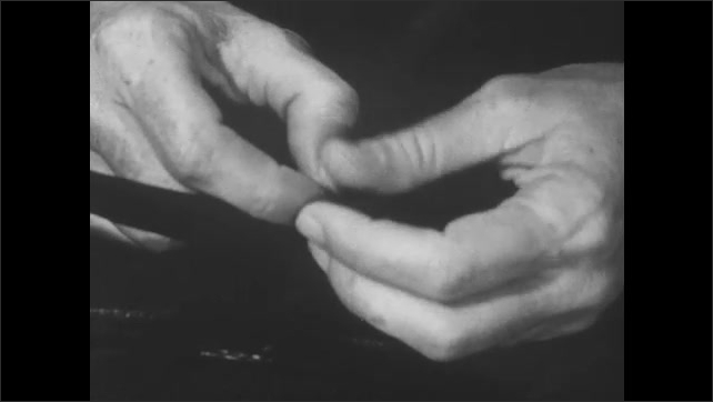 1950s: UNITED STATES: fingers rub together. Hands fiddle with threads