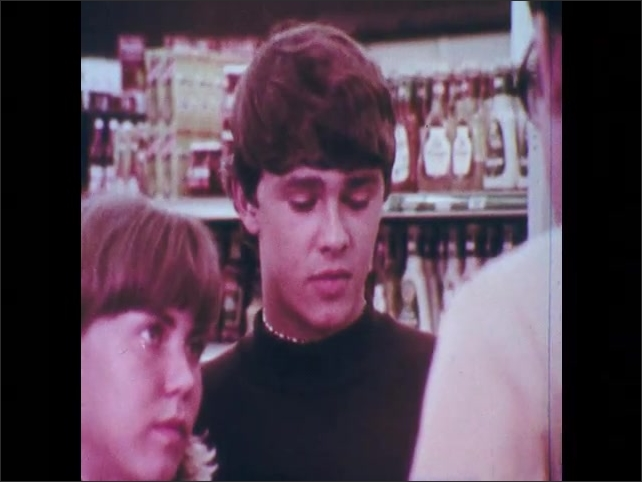 1970s: Teenage boy and girl talk to clerk.