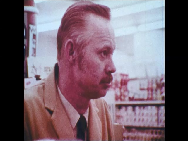 1970s: Store clerk talks to teenager in white tuxedo, teen shakes head no.
