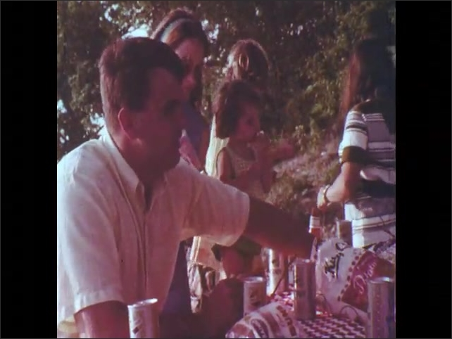 1970s: Men, women, and children enjoy a picnic outside, sit around picnic table, eat and drink.
