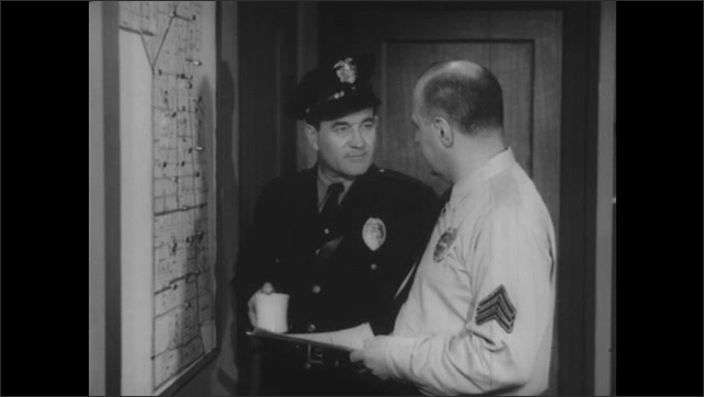 1950s: Sergeant sticks black pins in map on wall. Policeman joins him and they talk and gesture towards the map.