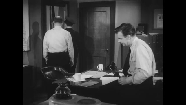 1950s: Policeman spills black map pins on to desk. Sergeant puts a hand on his shoulder and leads policeman to the door.