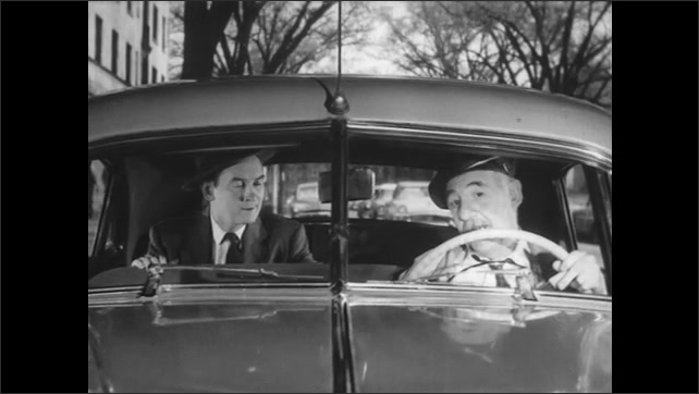 1950s: Courtesy Cab is parked at curb. Impatient passenger in back seat talks to driver. Driver replies calmly. Driver pulls car out in to road.