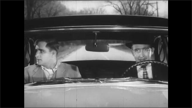 1950s: Car speeds along road. Passenger looks frightened and talks sharply to driver. Driver passes car unsafely and passenger looks back.