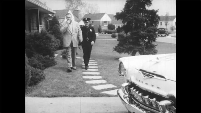 1950s: Man looks concerned. Man and police officer walk to car. Man and police officer examine headlight of car.