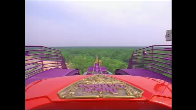 1990s: Roller coaster approaches top of track.  Raft navigates waterway under roller coaster.
