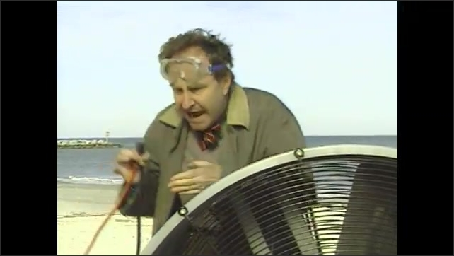 1990s: Man holding power cord speaks. Man puts on safety glasses and plugs in extension cord. Fan turns on and man holds arms in front of face.
