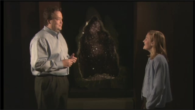 2000s: UNITED STATES: girl stands next to large rock and crystals. Man talks to girl by amethyst geode. Mineral and gemstone example.