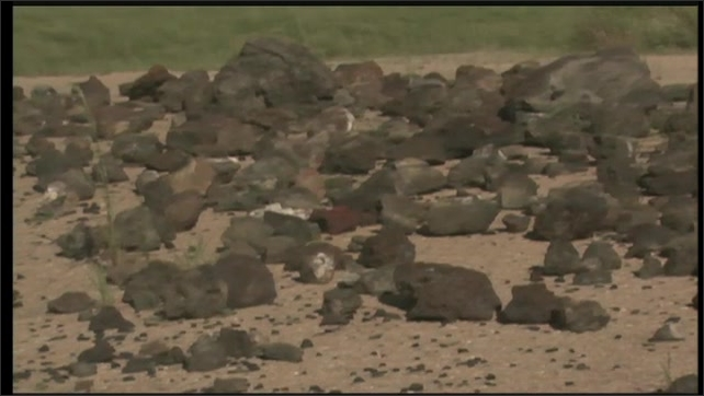 2000s: UNITED STATES: rocks on beach. People on beach.