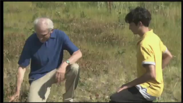 2000s: UNITED STATES: man and boy talk on mountain. Man puts on glasses. Man drives wedge into wood with hammer.