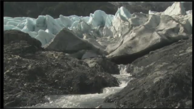 2000s: UNITED STATES: water and erosion under glacier. Fish in water animation.
