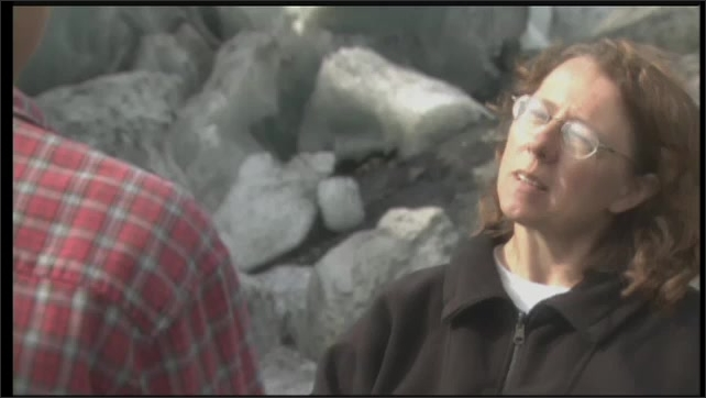2000s: UNITED STATES: lady gives smooth rock to boy. Lady and man walk across glacier in Alaska. Animation of erosion and abrasion.