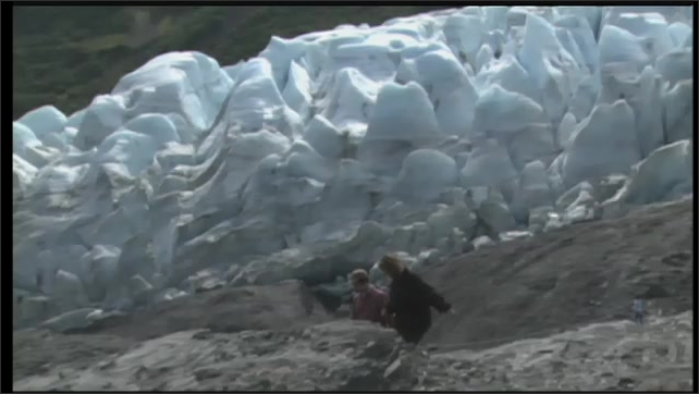 2000s: UNITED STATES: lady and boy walk by glacier in Alaska. Wind blown sand erodes rock.
