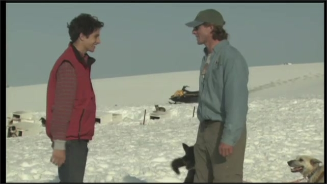 2000s: UNITED STATES: man holds husky puppy. Man and boy shake hands on snow. Husky dogs prepare to go mushing.
