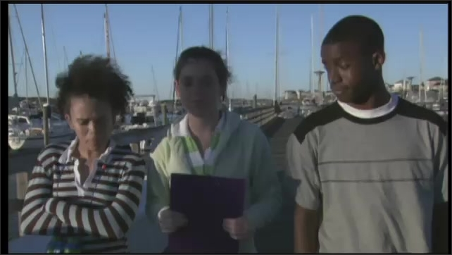 2000s: UNITED STATES: girl talks to boy. Teenagers walk by marina with clipboard. Boats in marina.