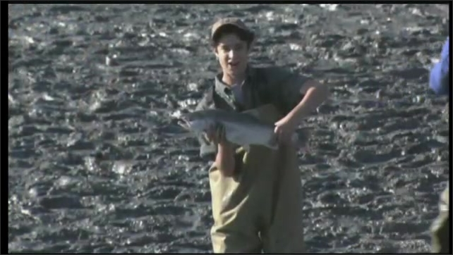 2000s: UNITED STATES: salmon on end of fishing line. Boy catches salmon. Boy holds up fish.