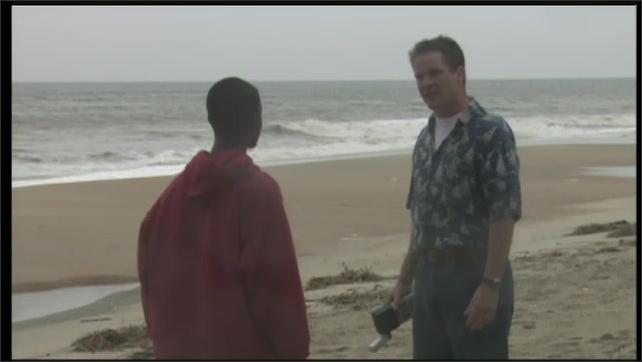 2000s: UNITED STATES: boy talks to man on beach. Vehicle on beach.