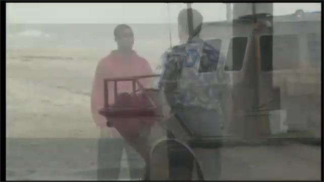2000s: UNITED STATES: amphibious vehicle on beach. Boy talks to man on beach.