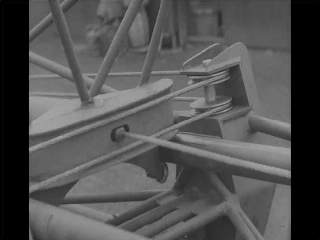 1940s: Men next to catapult. Close ups of wire tightening in catapult.