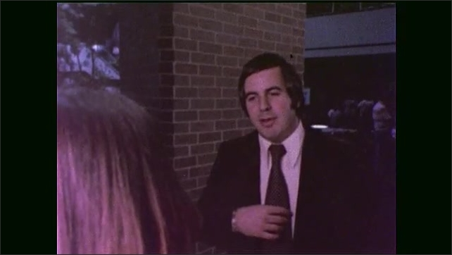 1970s: man with necktie steps to registration desk inside Houston hotel, reaches inside suit jacket and talks with woman in vest behind counter.