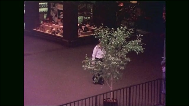 1970s: man in collar shirt walks around level of Houston Galleria near shoe store, looks at shops, passes men and women and leans against balcony railing.