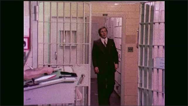 1970s: Man talks and walks through jail.  Guard sits at desk.