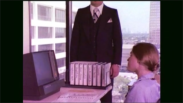 "1970s: Office.  Man stands and speaks.  Woman works on computer.  Man opens card and points.  Text reads ""A SERIES OF 8 FILMS ON WHITE COLLAR CRIME."""